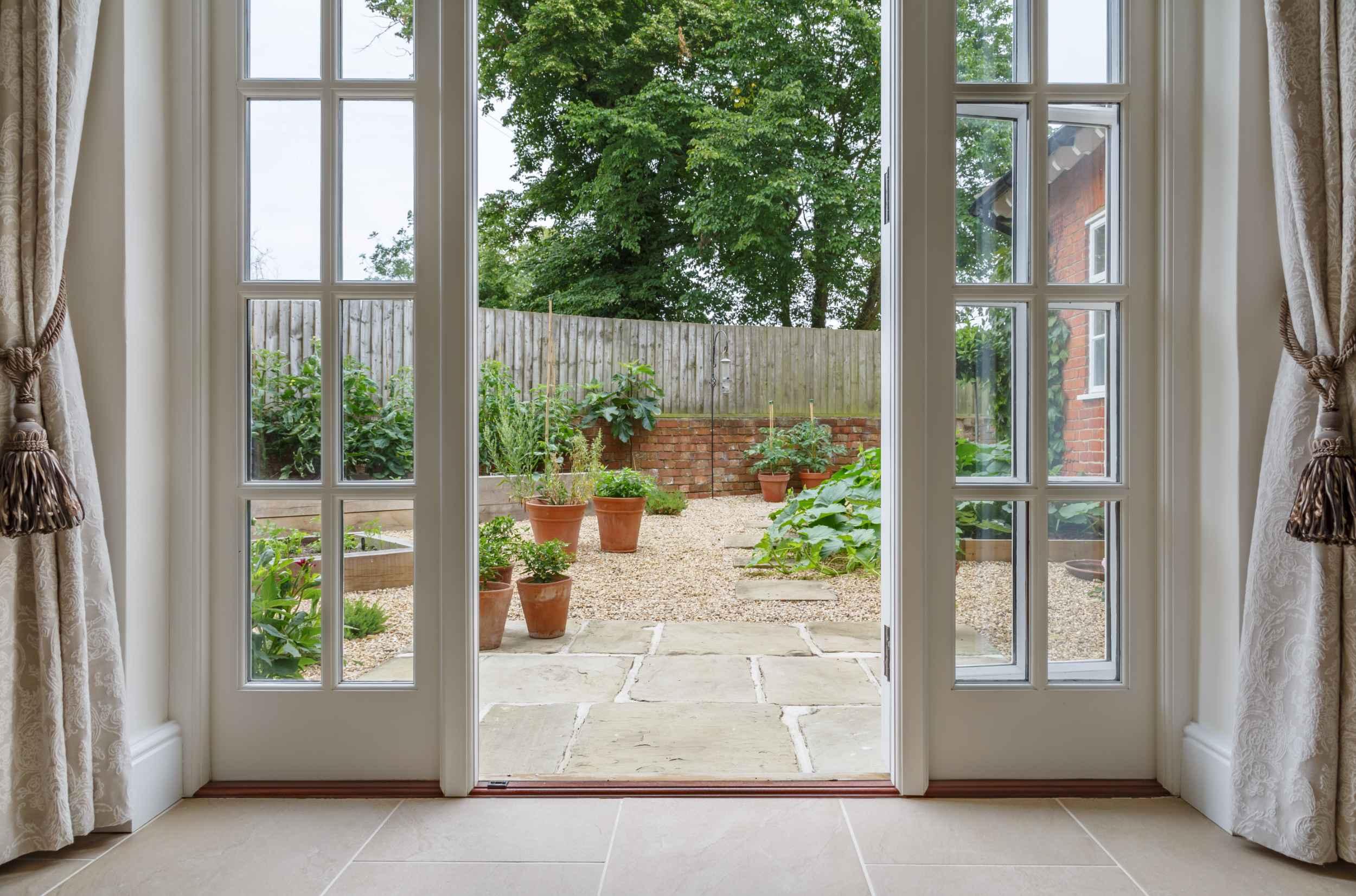 Blick in den Garten durch ein offenes Fenster